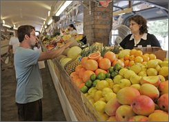 A man shops for fruit at a stand at the West Side Market in Cleveland, Wednesday, July 16, 2008. Food prices showed a big increase in June, rising by 0.7 percent, more than double the 0.3 percent increase of May. Vegetable prices shot up by 6.1 percent, the biggest increase in nearly three years. (AP Photo/Mark Duncan)