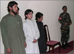 In this Nov 25, 2004 file photo, captured Central Asians alleged to be Islamic militants, Abdul Qahar, 26, Mohammad Khalid, 16, and Hussain 14,  from left, are presented before the media as an officer of Pakistan army looks on, in Peshawar, Pakistan. Afghanistan has been drawing a fresh influx of foreign jihadi fighters from Turkey, Central Asia, Chechnya and the Middle East, in one more sign that al-Qaida is regrouping on what is fast becoming the most active front of the war on terror.  (AP Photo/M. Sajjad, File)