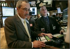 Traders Richard Farrell, left, and Christopher Carrella, both with Kellogg Specialist Group, work at computer terminals during early trading at the New York Stock Exchange, Thursday July17, 2008. The Dow Jones industrial average rose more than 100 points after Wall Street extended its rally into a second session.  (AP Photos/Bebeto Matthews)