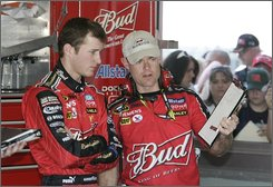 "In this Feb. 9, 2008 file poto, NASCAR driver Kasey Kahne, left, talks with crew chief Kenny Francis during practice for the Daytona 500 auto race at the Daytona International Speedway in Daytona Beach, Fla. For years, the folks at Anheuser-Busch have spent lavishly to remind fans that nothing goes better while watching the big game than a 6-pack brought to you by (insert Harry Caray impersonation here) ""your good friends at Budweiser.""  (AP Photo/Reinhold Matay, File)"