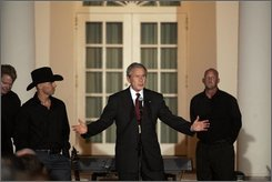 President Bush speaks as county music entertainer Kenny Chesney, second from left, and a members of his band watch in the Rose Garden of the White House, Wednesday, July 16, 2008, in Washington after President Bush hosted a social dinner in honor of Major League Baseball. (AP Photo/Haraz N. Ghanbari)