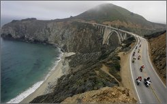 In this handout photo provided by the Monterey County Convention & Visitors Bureau, motorcycle enthusiasts escorted by a motorcycle California Highway Patrol ride over the Bixby Bridge into Big Sur marking the first group ride along scenic California Highway 1 since the start of the recent wildfires, Thursday, July 17, 2008 in Big Sur, Calif.  Highway 1 officially reopened in both directions Sunday, July 13.    (AP Photo/Monterey County Convention & Visitors Bureau, Tony Avelar)