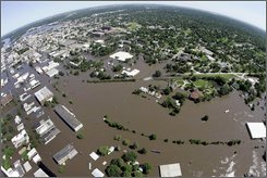 This June 14, 2008 file photo shows floodwaters  in Cedar Rapids, Iowa. Weeks after the latest massive floods in the Midwest, voluntary buyouts are again being considered in at least five states -- Missouri, Iowa, Wisconsin, Indiana and Illinois.   Officials in Cedar Rapids, Iowa, have been telling residents it could be a year or more before they know how much will be available for buyouts. Officials have said that half of the estimated 4,000 homes that were damaged will have to be demolished. (AP Photo/Jeff Roberson, File)