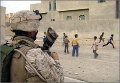 In this Sunday, April 8, 2007 file photo, a U.S. marine watches children play in Ramadi, in Iraq's Anbar province, 115 kilometers (70 miles) west of Baghdad. Iraq says it wants to be in charge of security in the entire country by the end of the year. But a crucial place stands in the way