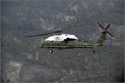 In this July 17, 2008 file photo, President Bush rides on Marine One for a tour of the California wildfires in Redding, Calif. John McCain and Barack Obama vow to reform the nation's defense procurement process if elected president, yet each is unwilling to take a firm stand against the skyrocketing cost of a plum White House perk