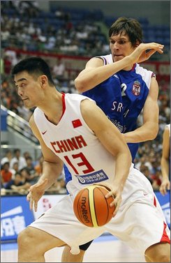 China's Yao Ming (13) aims to score as Serbia's Boban Marjanovic, in blue jersey, blocks during their match of the Stankovic Cup international basketball tournament Thursday, July 17, 2008, in Hangzhou, China. Russia, Angola, Serbia, and China are competing in the tournament which is a warm-up for the Olympic Games. China won 96- 72. (AP Photo/Eugene Hoshiko)