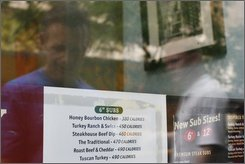 A restaurant window menu displays the calorie count for each food item, in New York, Friday July 18, 2008. Several fast food chains say they have finally begun obeying a new city rule requiring some restaurants to post calorie counts right on the menu (AP Photo/Ed Ou)