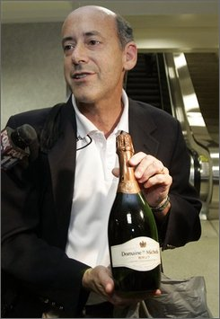 Craig Tornberg, general manager of the New England Revolution Major League Soccer team, shows a bottle of champagne, a gift from a flight attendant, as he describes the scene aboard an American Airlines flight, en route from Boston to Los Angeles, when a man emerged, naked, from a lavatory and had to be subdued by him and other team members, upon arrival at  Los Angeles International Airport Friday, July 18, 2008. (AP Photo/Reed Saxon)