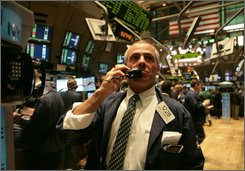 Frank Cannarozzo, a trader with B & B Securities, talks on a traders phone as he works during early trading at the New York Stock Exchange, Thursday July17, 2008. The Dow Jones industrial average rose more than 100 points after Wall Street extended its rally into a second session.  (AP Photos/Bebeto Matthews)
