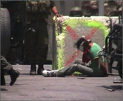 In this image from video shot by a Palestinian activist and released by the Israeli human rights group B'Tselem on Monday, July 21, 2008, an Israeli soldier stands next to a handcuffed and blindfolded Palestinian, sitting on the ground, during a demonstration against Israel's separation barrier in the West Bank village of Nilin, near Modin, July 7, 2008. A video released by an Israeli human rights group has sparked a military investigation into the abuse of the Palestinian protester by an Israeli soldier. The video released by B'Tselem shows a soldier firing a rubber-coated bullet near the foot of a West Bank man whose hands were bound and whose eyes were blindfolded. The group says 27-year-old Ashraf Abu Rahma was lightly wounded and was not hospitalized. (AP Photo/B'Tselem, HO)