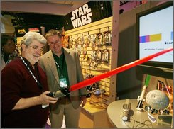"In this Feb. 10, 2007 file photo provided by Hasbro, filmmaker George Lucas, left, tries out a Star Wars 'Force Action Light Saber' shown to him by Derryl DePriest, right, director of marketing for Hasbro's Star Wars line in their showroom at the American International Toy Fair in New York.  Toymaker Hasbro Inc. said Monday, July 21, 2008, second-quarter profit rose, helped by demand for ""Star Wars""- and ""Indiana Jones""- related toys and the benefit of a weaker dollar.  (AP Photo/Hasbro, Ray Stubblebine, File)"