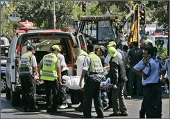 Israeli rescue workers remove the body of a Palestinian driver that rammed a construction vehicle into three cars and a bus in Jerusalem, Tuesday, July 22, 2008. A Palestinian from East Jerusalem rammed the vehicle into three cars and a city bus in downtown Jerusalem on Tuesday, wounding four people before he was shot dead, in a chilling imitation of a similar attack that took place in the city earlier this month. (AP Photo/Sebastian Scheiner)
