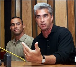 In this July 21, 2000 file photo, Cuban baseball player Andy Morales, left, listens in as sports agent Gus Dominguez, right, speaks of Morales' chances of  playing professional baseball in the U.S. during a news conference at a restaurant in Miami's Little Havana area. Dominguez is serving a five-year sentence as the first sports agent convicted of illegally smuggling a Cuban player into the United States.  (AP Photo/Tony Gutierrez, file)