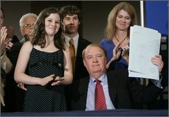 Acting New Jersey Gov. Richard J. Codey, center, holds up a bill he signed at Saint Barnabas Medical Center in Livingston, N.J.,  Tuesday, July 22, 2008, that would make New Jerseyans getting driver's licenses decide whether they will be an organ donor. The state has five years to  implement the program which includes teaching high school students  about organ donation beginning with the 2009-10 school year. Standing next to from left; Codey are Megan Bottino, 13,  her brother Joseph F. Bottino III, 15, and their mother, Dianne Bottino, whose husband Joseph F. Bottino Jr. died while waiting for an organ donation. (AP Photo/Mike Derer)