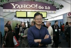 In this Jan. 7, 2008 file photo, Yahoo CEO Jerry Yang poses for a photo in front of the Yahoo booth at the Consumer Electronics Show in Las Vegas. Yahoo says its second-quarter profit dropped 18 percent, Tuesday, July 22, 2008. It marks the latest in a long stretch of disappointing results for the Internet company. (AP Photo/Paul Sakuma, file)