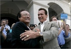 Gov. Arnold Schwarzenegger, right, shakes hands with Orange Cove Mayor Victor Lopez, during a water rally held at the Capitol in Sacramento, Calif., Wednesday, July 23, 2008.  More than 500 farm workers and their families rallied to call for the Legislature to approve a measure to  place of a $9.3 billion water bond measure on the November ballot to build reservoirs, encourage conservation and restore the Sacramento-San Joaquin Delta. (AP Photo/Rich Pedroncelli)