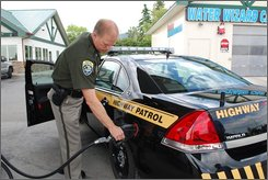 Col. Paul Grimstad, head of Montana's Highway Patrol fills up his cruiser in Helena, Montana, in July 2008.  With gas prices soaring, state police agencies nationwide are scrambling to find the money to cover costs -- in some cases looking to downsize to smaller-engine cars or even motorcycles. (AP Photo/ Christina Almeida)