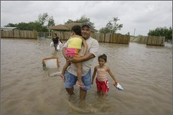 Robert Sanchez, second from right, carries his daughter, Renee Sanchez through the flood waters to their home as his wife Joangela Sanchez and their daughter Jovanna Sanchez following a shopping trip after Hurricane Dolly, Thursday, July 24, 2008, in the Laureles area of Cameron County, Texas. (AP Photo/Matt Slocum)