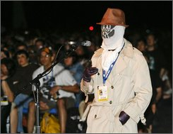 "Ben Williams dressed as one of the Watchmen asks a question during a panel discussion for the new movie ""Watchmen"" at the Comic-Con 2008 convention Friday, July 25, 2008 in San Diego.  (AP Photo/Denis Poroy)"