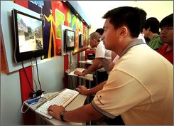 In this July 2, 2007 file photo, visitors play on-line shooting game at an international animation, cartoon and game fair in Shanghai, China.  China's booming Internet population has surpassed the United States to become the world's biggest, with 253 million people online despite government controls on Web use, according to government data reported Friday, July 25, 2008. (AP Photo/ Eugene Hoshiko, File)