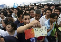 A man displays a ticket to next month's Olympic Games while waiting in a crowd to buy more, outside a ticket office in Beijing early Friday July 25, 2008. Thousands waited overnight for a chance to buy tickets from the last batch of Olympic tickets which went on sale Friday morning. (AP Photo/Greg Baker)