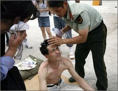 A Chinese paramilitary police officer, right, helps a man cool off outside a ticket office in Beijing, China, Friday, July 25, 2008. The man was waiting in line to buy tickets to next month's Olympic Games. Eager fans swarmed and in some cases scuffled as they lined up at sales windows Friday to get the final batch of tickets for next month's Olympics. (AP Photo/Andy Wong)