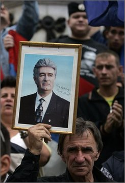 A protester holds a picture of a war crimes suspect Radovan Karadzic, during a rally condemning his arrest , in downtown Belgrade, Serbia, Thursday, July 24, 2008. Karadzic, who was captured in Belgrade on Monday and is awaiting extradition to the U.N. war crimes tribunal in The Hague, Netherlands. (AP Photo/Darko Bandic)