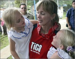 U.S. citizen Chere Lyn Tomayko, center, holds her two Costa Rican born daughters, after receiving asylum in Costa Rica, in San Jose, Friday, July 25, 2008.  Tomayko, wanted by the FBI for international parental kidnapping, has been awarded asylum in Costa Rica and cannot be extradited to the United States. Tomayko, who is now married to a Costa Rican doctor and has two Costa Rica-born children, told authorities she moved to the Central American country because she had been physically abused by her ex-boyfriend. (AP Photo/Str)