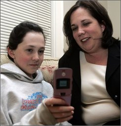 This Jan. 25, 2008 file photo shows  Meghan Mulvany, 12, left, and her mother, Kate Mulvany, as they look at Meghan's cell phone at their home in Stamford, Conn.  Kate says that although Meghan wanted the phone for social and status reasons, ultimately Kate got her the phone for safety reasons.   (AP Photo/Bob Child, FILE)