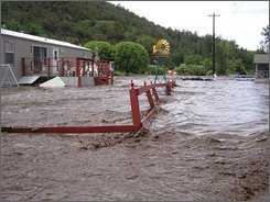This photo provided by Ruidoso News shows flood waters destroying yards and fences of homes at River Ranch RV Park, along Highway 70 between Glencoe and Ruidoso Downs, N.M. on July 27, 2007. About 300 people -- both residents and tourists -- were evacuated from homes, campgrounds and a recreational vehicle park as flooding hit around the resort town of Ruidoso after the remnants of Hurricane Dolly dumped an estimated six inches on the mountainous area. (AP Photo/Courtesy of Marty Racine, Ruidoso News)