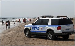A New York City Police Department vehicle drives down the Coney Island beach in Brooklyn, New York, Sunday, July 27, 2008. The police were searching for a ten-year-old girl who went missing July 26. Four swimmers drowned and three were missing Saturday in two days of treacherous ocean currents at Long Island and New York City beaches, authorities said.  (AP Photo/Henny Ray Abrams)