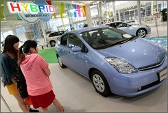 "Visitors look at Toyota Motor Corp.'s hybrid car ""Prius"" displayed at showroom Toyota Mega Web in Tokyo Wednesday, July 23, 2008. Japan's top-seller Toyota lowered its global vehicle sales plan for this year to 9.5 million vehicles -- down from 9.85 million -- as the sluggish North American market slows the Japanese automaker's momentum. Even with the lower number announced Monday, July 28, 2008, Toyota plans to sell more vehicles than it did last year. (AP Photo/Itsuo Inouye)"