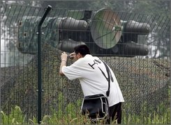 "A Chinese man takes pictures near a camouflaged surface-to-air missile launcher station near the Olympic National Stadium, also known as Bird's Nest, in Beijing, China, Friday, July 25, 2008. A vast security apparatus has been charged with guarding Beijing during the Aug. 8-24 Olympics games, including thousands of soldiers, police officers and anti-terrorist squads. The government has also declared a ""people's war"" against those who could disrupt the games, enlisting the help of neighborhood watch groups to root out threats. (AP Photo/Andy Wong)"