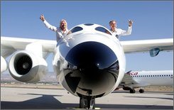 "Virgin Galactic founder Sir Richard Branson, left, and Scaled Composites LLC founder Burt Rutan wave from the mothership aircraft White Knight Two ""Eve"" during an unveiling ceremony at Scaled Composites hangar in Mojave, Calif. Monday, July 28, 2008.  More than 250 customers have paid $200,000 or put down a deposit for the chance to be one of Virgin Galactic's first space tourists. A date for the first launch has yet to be announced.  (AP Photo/Stefano Paltera)"