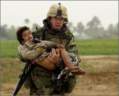 Pfc. Joseph Dwyer, 26, from Mt. Sinai, N.Y., carries a young Iraqi boy who was injured during a heavy battle between the U.S. Army's 7th Cavalry Regiment and Iraqi forces in this March 25, 2003 file photo near Al Faysaliyah, Iraq. Dwyer died of an accidental overdose after struggling with post-traumatic stress disorder for almost five years. (AP Photo/Warren Zinn, Army Times)