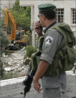 An Israeli border police officer stands on a rooftop as municipality workers demolish a house in which according to Israeli authorities, four floors were built without a permit, in the east Jerusalem neighborhood of Beit Hanina, Monday, July 28, 2008. According to Palestinian residents of the house, the building permit was revoked by Israeli authorities. Jerusalem's municipality had no comment. (AP Photo/Sebastian Scheiner)