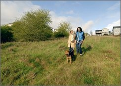 Laura Whorton, right, and Karen MacDonald walk Apple the dog through a park atop Clastop Butte on the Waterleaf property in Portland, Ore., Tuesday, April 29, 2008.  The 27-acre parcel, which was purchased from the developer by The Trust for Public Land after the housing market fell, was added to an existing, nearby city park in Portland.  Since last fall, the trust has preserved nearly 1,000 acres once targeted for housing in Georgia, New Hampshire, Oregon, Minnesota and Massachusetts. (AP Photo/The Trust for Public Land, Darcy Kiefel)
