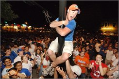 In this April 2, 2007 picture provided by the University of Florida, a University of Florida student attempts to climb a greased light pole among a crowd of fans in the streets of Gainesville, Fla. moments after the men's UF basketball team won its second consecutive championship win. The University of Florida can raise a glass to another national title - best party school in the country. The Gators, known for wild celebrations following national championships in football and basketball, wrested the party title away from West Virginia University and beat out the University of Mississippi and Penn State University, in the Princeton Review survey of 120,000 students released Monday, July 28, 2008. (AP Photo/University of Florida, Kristen Bartlett Grace)