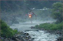 A helicopter loads water from the Merced river while making water drops on the Telegraph fire near Yosemite Valley Monday, July 28, 2008, outside of Mariposa, Calif. (AP Photo/Ron Lewis)