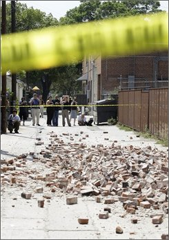People stand in an alleyway behind police tape near where bricks fell from an unoccupied building during an earthquake Tuesday, July 29, 2008, in Pomona, Calf., near Los Angeles. The 5.4-magnitude quake was felt from Los Angeles to San Diego, and as far east as Las Vegas, 230 miles away. (AP Photo/Ted S. Warren)