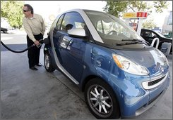 In this July 28, 2008 file photo, Larry Syres fills up his Smart car in Palo Alto, Calif.. Syres says he fills up his 8.7 gallon gas tank and that he averages 42 miles per gallon. Daimler AG on Friday, Aug. 1, 2008 said that U.S. sales for its Mercedes-Benz Car division rose in July as economy-minded urban dwellers boosted sales of the German automaker's ultra-small Smart Fortwo vehicles. (AP Photo/Paul Sakuma, file)