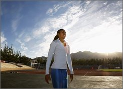 U.S. 100-meter runner Torri Edwards walks beside the track during her evening practice for the upcoming Beijing Olympic Games at a university in Dalian, Liaoning province, China, Saturday, Aug. 2, 2008. (AP Photo/Andy Wong)