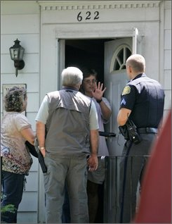 Frederick Police talk with a woman who they identified as Diane Ivins, the widow of Bruce E. Ivins, 62, who died Tuesday of an apparent overdose of prescription Tylenol mixed with codeine, at their home, Friday, Aug. 1, 2008, in Frederick, Md. Ivins, a top U.S. biodefense researcher who, according to his brother, was being aggressively pursued by the FBI in connection with a series of anthrax mailings after the Sept. 11, 2001 terrorist attacks apparently committed suicide. (AP Photo/Rob Carr)