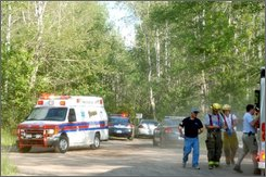 Beacon Ambulance, Kingsford Public Saftey Officers and volunteer firefighters at the entrance to the East Kingsford Train bridge in Kingsford, Mich., where at least four people were shot Thursday evening, July 31, 2008. Authorities in Marinette County, Wis., say three people are dead and one wounded in shootings that occurred in the Wisconsin-Michigan border area. (AP Photo/Iron Moutain Daily News, Theresa Peterson)
