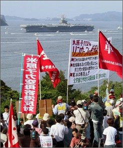 In this May 25, 2006 file photo, Japanese protesters shout slogans as U.S. nuclear-powered  aircraft carrier USS Abraham Lincoln enters Sasebo port, western Japan. Japan's Foreign Ministry said Saturday, Aug. 2, 2008, the U.S. Navy had told it that a small amount of radiation might have leaked from the nuclear-powered USS Houston as it traveled around the Pacific. The Houston made calls in March and April in the southern Japanese naval ports of Sasebo and Okinawa. (AP Photo/Kyodo News, File)