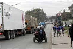 An onion vendor pulls his cart in a traffic jam in Naiorbi, Kenya, as some motorists take to the wrong side of the road to get by, rear, July 2, , 2008.  (AP Photo/Sayyid Azim)