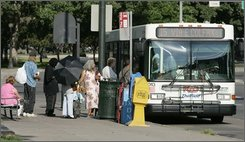 Passengers board a RTD bus in downtown Denver on Thursday, July 17, 2008. Faced with an increase in ridership, RTD officials have looked to cut routes, which has triggered protests from users of the transportation system. People are using public transportation more than ever, but higher fuel costs -- and lower sales tax revenues -- are forcing them to trim routes, sometimes at the very expense of people who increasingly depend on them. (AP Photo/Ed Andrieski)