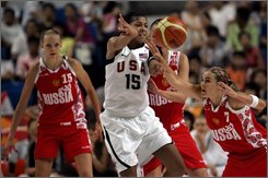 South Dakota native  and Russia's  guard Becky Hammon, left, tries to  block by US forward Candance Parker, center as Russia's  center Irina Psipova looks on during a basketball  game between the US and Russia at the Women Diamond Ball Basketball tournament, a warm up for the Olympics, in Haining, China, Monday, Aug. 4, 2008. Hammon wasn't in the 29 player pool used to select the US Olympic team. So she chose another option