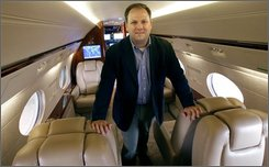 Justin Sullivan, a private jet broker and founder of Regent Jet, poses onboard a Gulfstream IV he leases at Pease International Airport in Portsmouth, N.H., Wednesday July 30, 2008.  Sullivan has noticed that some wealthy clients have cut back from from private jets to smaller propeller airplanes and picking up sandwiches on their own instead of catering in-flight meals as the impact of a slower economy hits the higher income earners. (AP Photo/Charles Krupa)
