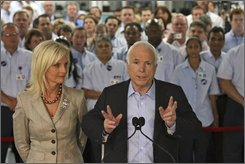 Republican presidential candidate, Sen. John McCain, R-Ariz., right, and his wife Cindy are framed by employees of the  National Label Company as he speaks to reporters after a tour of the factory, Monday, Aug. 4, 200 in Lafayette Hill, Pa.  (AP Photo/Mary Altaffer)